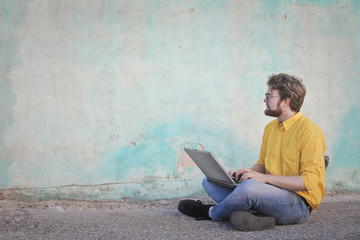Guy sitting on the floor with laptop
