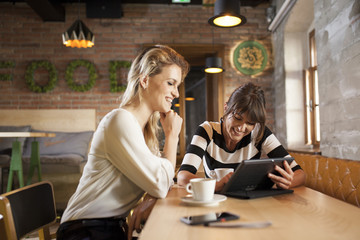 Two girlfriends using digital tablet in coffee shop