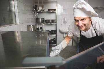 Smiling chef opening oven