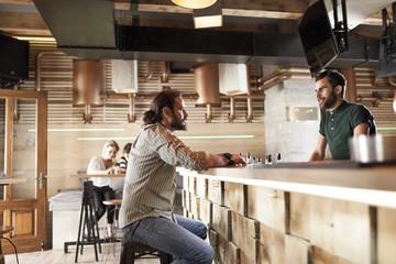 Man in coffee shop talking to bartender