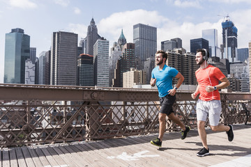 USA, New York City, two men running on Brooklyn Brige