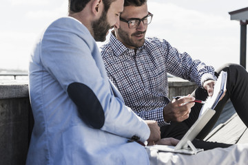 Two businessmen with notepad and tablet working outdoors