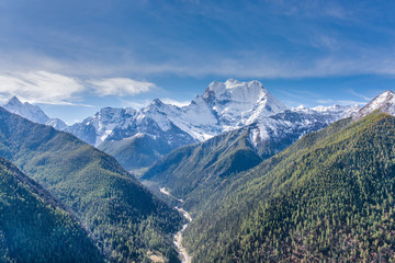 Mountain with snow and pine forest in a sunshine day of autumn,