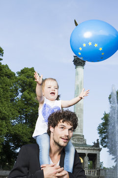 Girl on fathers shoulders catching balloon with European logo