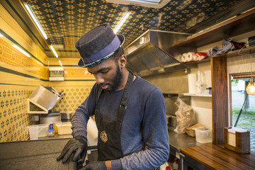 Man with hat and apron working in commercial kitchen of food truck