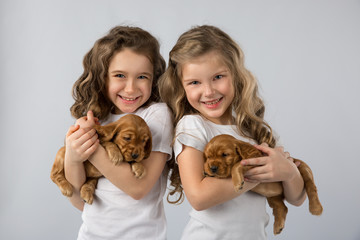 Cute children two little girls with red puppys isolated on white background. Kid Pet Friendship