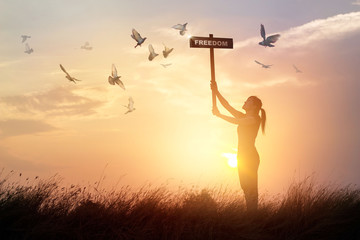 Fototapete - Woman holds a sign with word freedom and flying birds on sunset