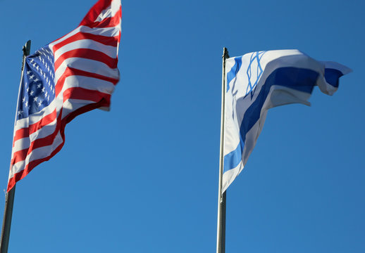 Flying in the blue sky American flag and the Israeli flag