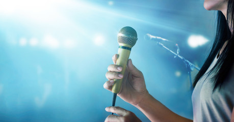 Woman holding microphone and singing on concert stage background