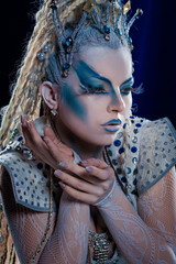 emotional actress woman in makeup and costume of the Snow Queen in the blue-black background