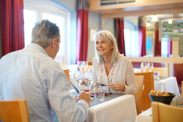 Senior couple sitting at restaurant table for dinner
