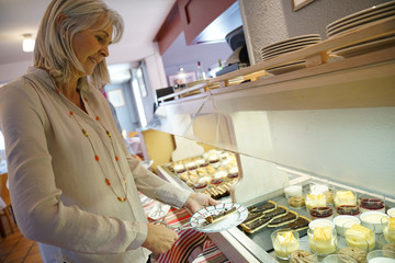 Senior woman in restaurant helping herself at delicatessen buffet