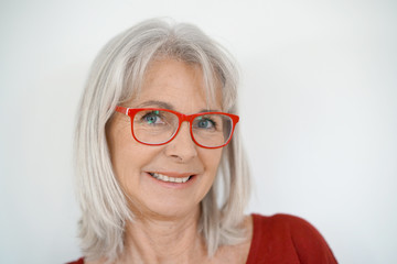 Portrait of senior woman with red shirt and eyeglasses, isolated