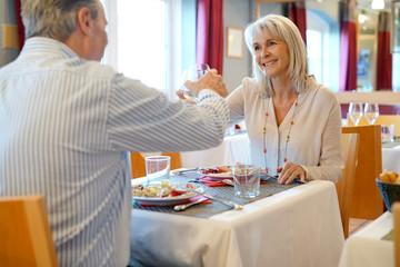 Senior couple having dinner in restaurant, cheering up