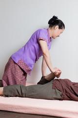 Asian massagist doing thai massage for caucasian woman in spa sa