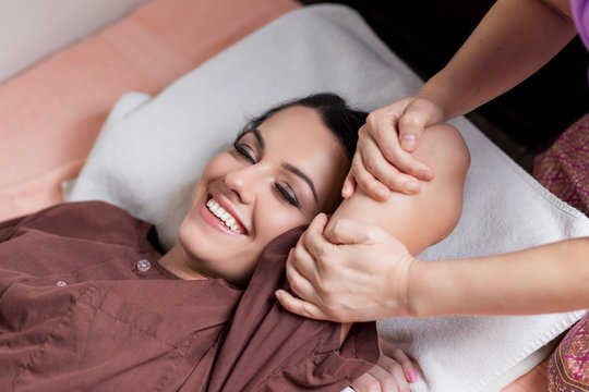 Young woman getting traditional thai hand stretching massage by