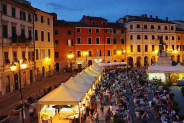 People tasting traditional Italian cuisine at the square - Piazza Giacomo Matteotti in Sarzana, Italy. View above night historical city.