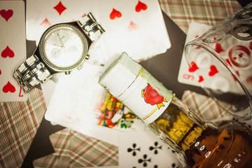 L'orologio, una bottiglia di whiskey sullo sfondo di carte da gioco