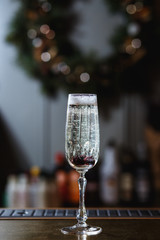A glass of sparkling wine with berries inside, on the bar stand. Christmas wreath in the background. Selective focus, small depth of field, film grain effect.