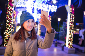 Woman taking selfie by mobile phone with xmas decoration