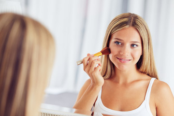 Smiling woman applying make up with a big brush and looking in the mirror. Focus on her reflection