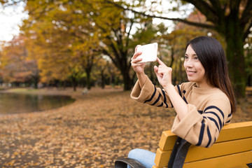 Woman using mobile phone to take photo at park