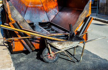 working tools for repairing city roads with bitumen and asphalt mix..wheelbarrow, shovel, rake