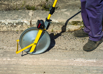 Surveyor with measuring wheel (odometer) detects the length of an excavation of minitrench..Close up odometer meter