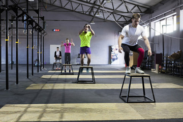Athletes doing box jumps in gym