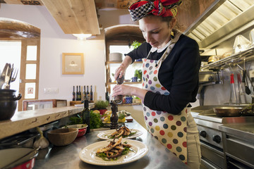 Female cook in restaurant seasoning food on plates