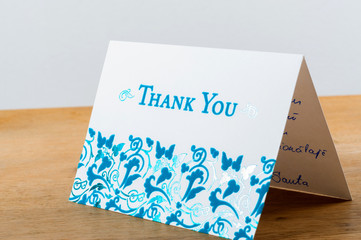 White thank you card with blue letters with note written by hand