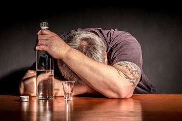 ein Mann sitzt mit einer Flasche Alkohol an einem Tisch