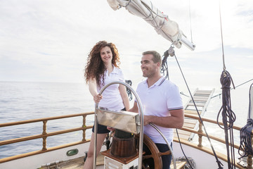 Young couple steering sailboat together