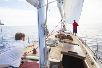 Man winding rope with cable winch on sailboat