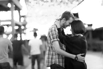 black and white photo happy loving couple in the evening against the background of light garlands