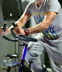 Sportive man on the spinning bicycle