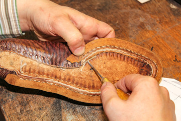 Repairing a brown leather shoe shows the craftsmanship of a Dutch shoemaker in Oegstgeest.