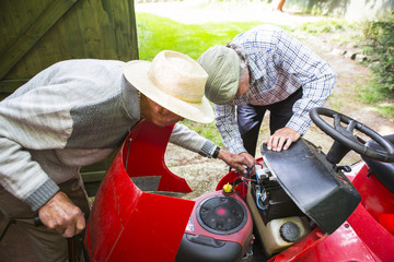 Senior Father and Son fixing together lawn mower