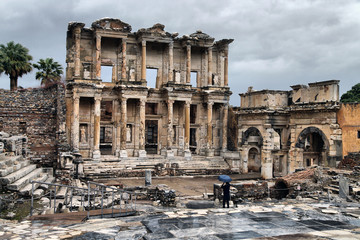 a tourist man is taking Ephesus Celsus Library's photo in a rainy day