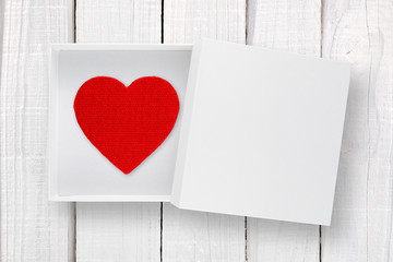 Red heart in white box with cover on white wooden background