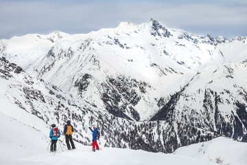 Group of snowboarders looking at mountain range
