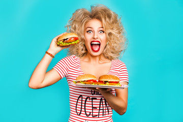 Studio fashion portrait of a beautiful funny young girl on the turquoise background, blonde holding a tray burger is going to bite a hamburger, curly hair, perfect makeup, crazy emotions, fast food