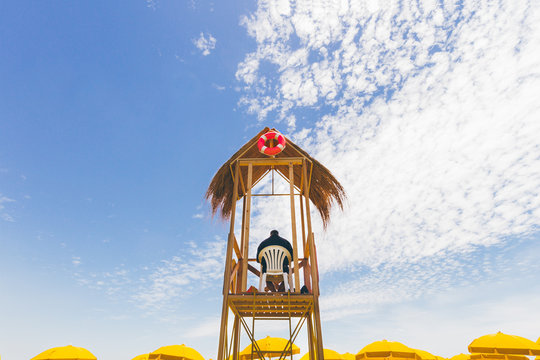 Lifeguard tower with ring buoy and yellow umbrellas