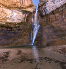 Lower Calf Creek Falls Reflection - A breath-taking, beautiful, cool, 130 foot desert waterfall at the end of a canyon grotto with a reflection in the transparent pond. Boulder, Utah.