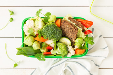 School or picnic lunch box with sandwich and vegetables