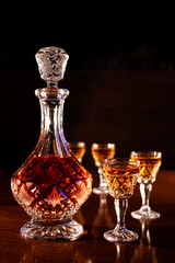 crystal decanter and glasses full of rum, carafe and a dram of alcohol on a wooden table, dark background