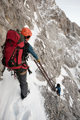 Two mountaineers climbing steep wall on safety ladder