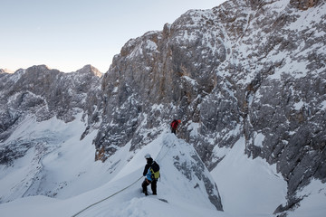 Two mountaineers moving up snowcapped cliff in mountain range