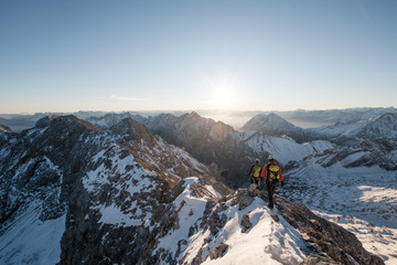 Two mountaineers climbing on mountain peak in European Alps
