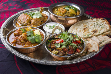 Traditional Indian Curry Dishes as close-up on Thali